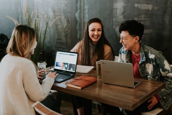 Lachende Frauen sitzen vor Laptop