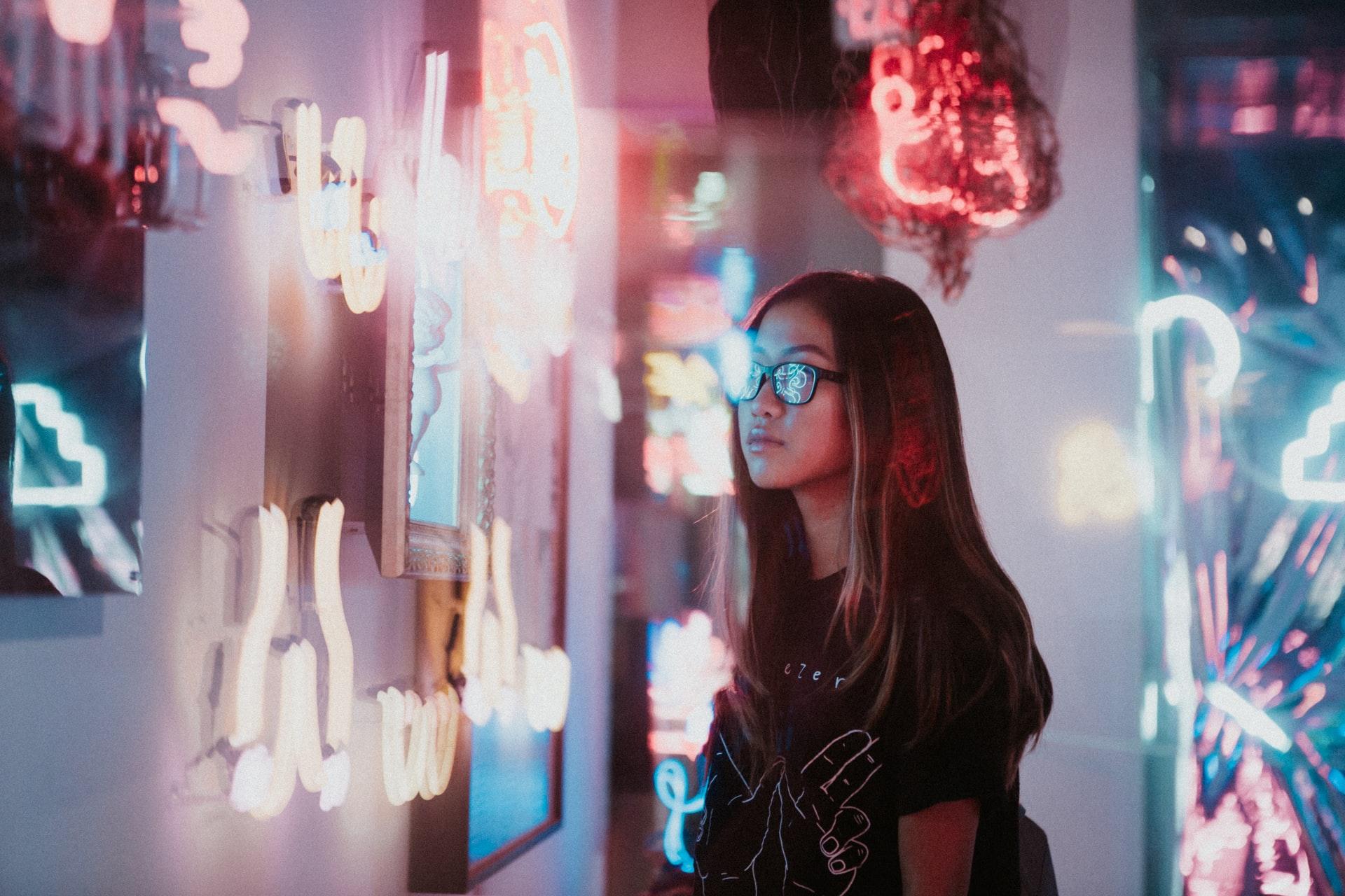 Frau steht neben Neon Zeichen