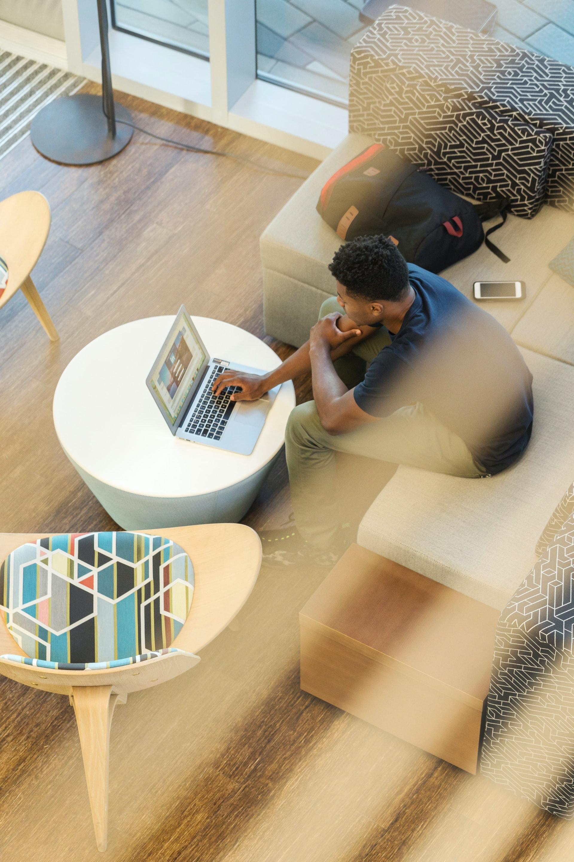 Mann sitzt auf Couch mit Laptop